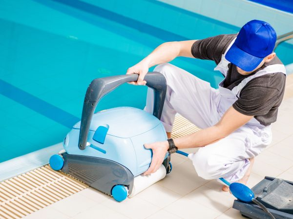 Pool Vacuum Cleaner. Caucasian Swimming Pools Technician with Cleaning Machine.