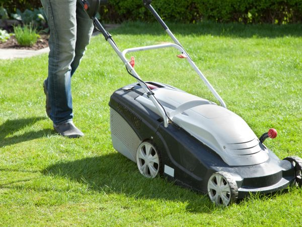 13585055 – outdoor shot of a man mowing the lawn
