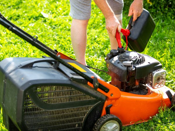Man refueling lawnmower on his huge garden, gardening concept