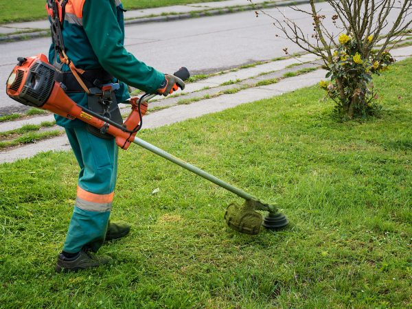 Man in overall and safety helmet trims overgrown grass by grass cutter